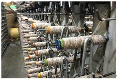多くの糸巻きから奥の織機に糸が送られる